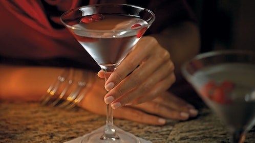 Woman holding martini glass inside a bar in New York