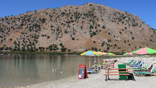 Nice view of lawn chairs and umbrellas on Lake Kournas in Kournas