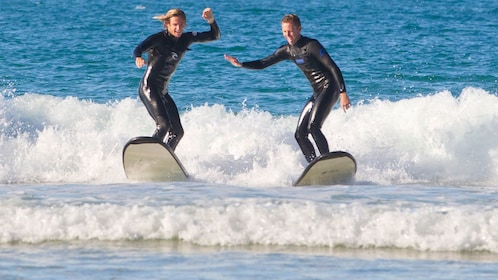 Two people having fun learning to surf at Torquay beach