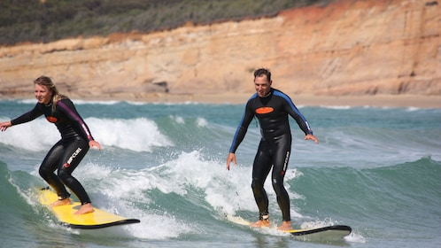Two people on a surfing lesson at Torquay beach