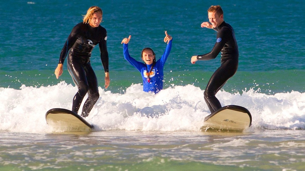 Show item 3 of 6. Three people on a surfing lesson at Torquay beach