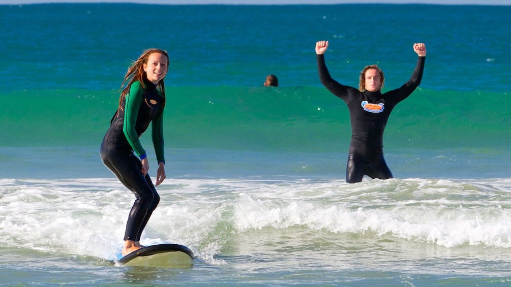 Show item 3 of 6. Couple learning how to surf at Anglesea