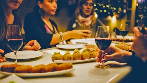 Friends at a table with food and wine in Barcelona Spain