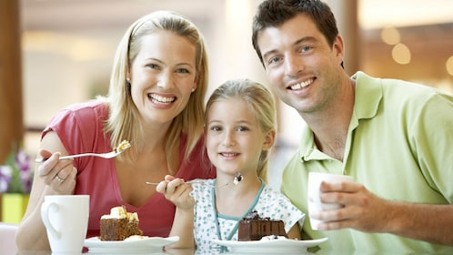 Family smiles for a picture while enjoying a meal together