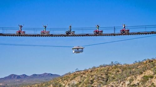 Riding ATVs across a narrow suspended bridge