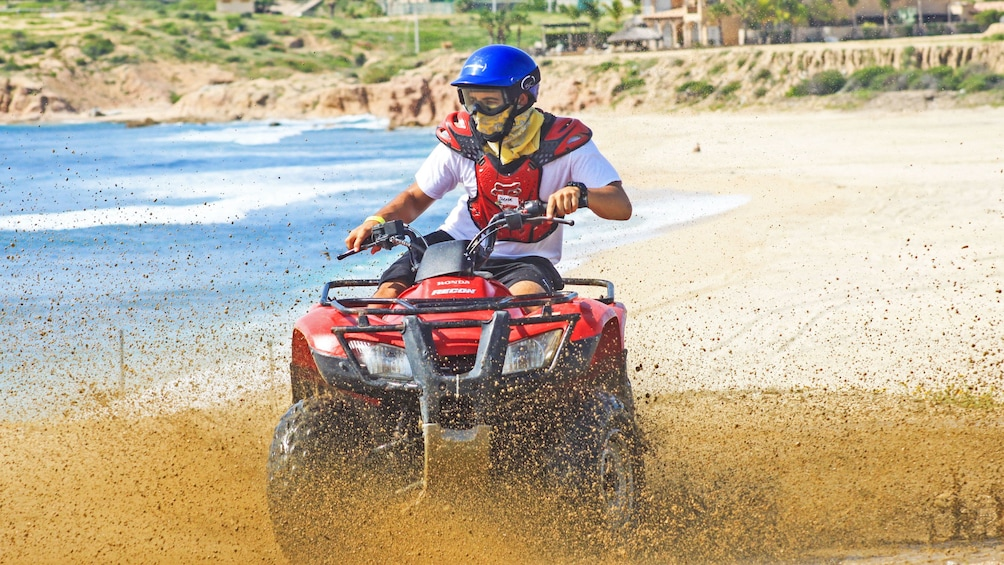 Show item 2 of 10. ATV splashing wet sand at the beach in Los Cabos