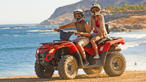 Couple riding an ATV at the beach in Los Cabos
