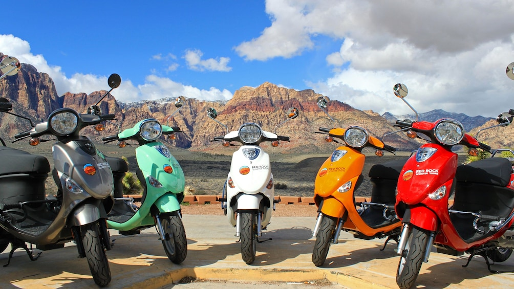 Åpne bilde 5 av 5. Colorful scooters with mountainous backdrop