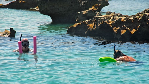 Snorkeling couple near large rocks emerging from the water in Bermuda