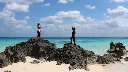 Women perched on volcanic rocks along the coast in Bermuda
