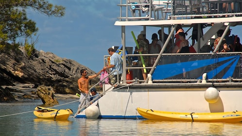 Passengers on the lower level of a power catamaran anchored off the shore of a small beach in Bermuda