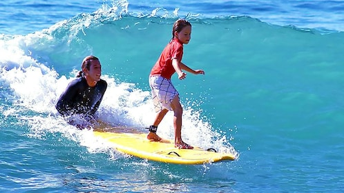 Child surfing with a guide in Los Cabos