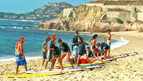 Group learning how to use the surfboard on land in Los Cabos