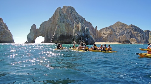 Group kayaking near the rock formations in Los Cabos