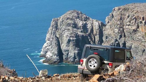 Jeep driving along rocky cliffs in Los Cabos