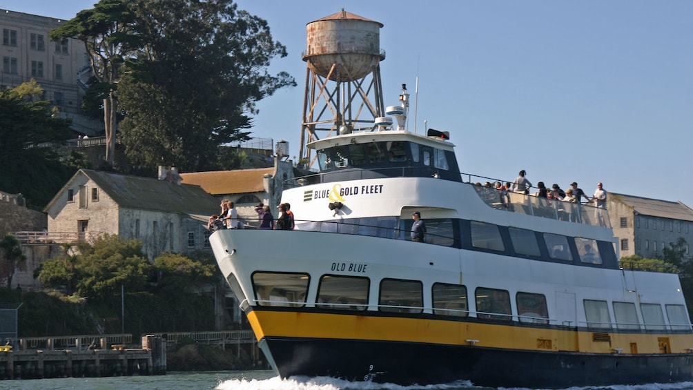 Show item 2 of 11. Tour boat passing by Alcatraz Island in San Francisco