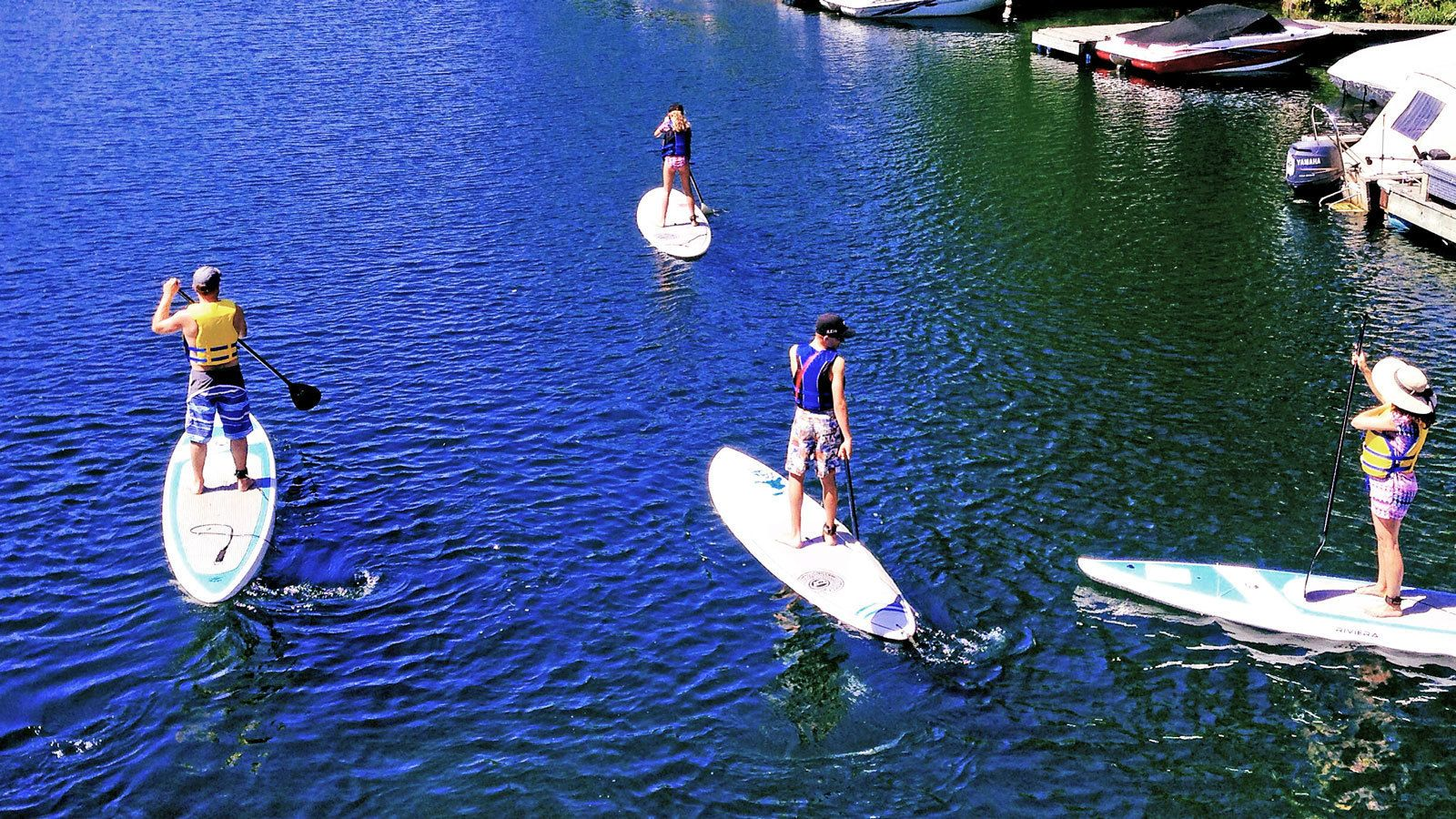 a group of paddleboarders near docked boats in Toronto