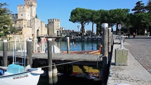 boating docks near an old stone castle in Lake Garda
