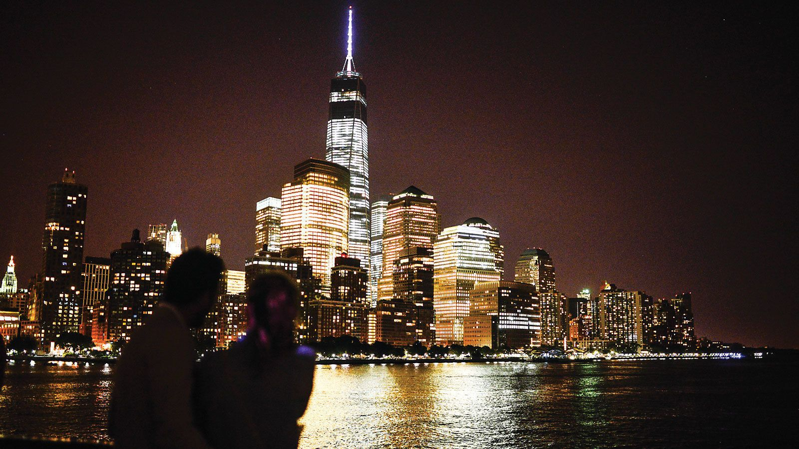 Silhouette of a couple looking at the city from a cruise at night in New York
