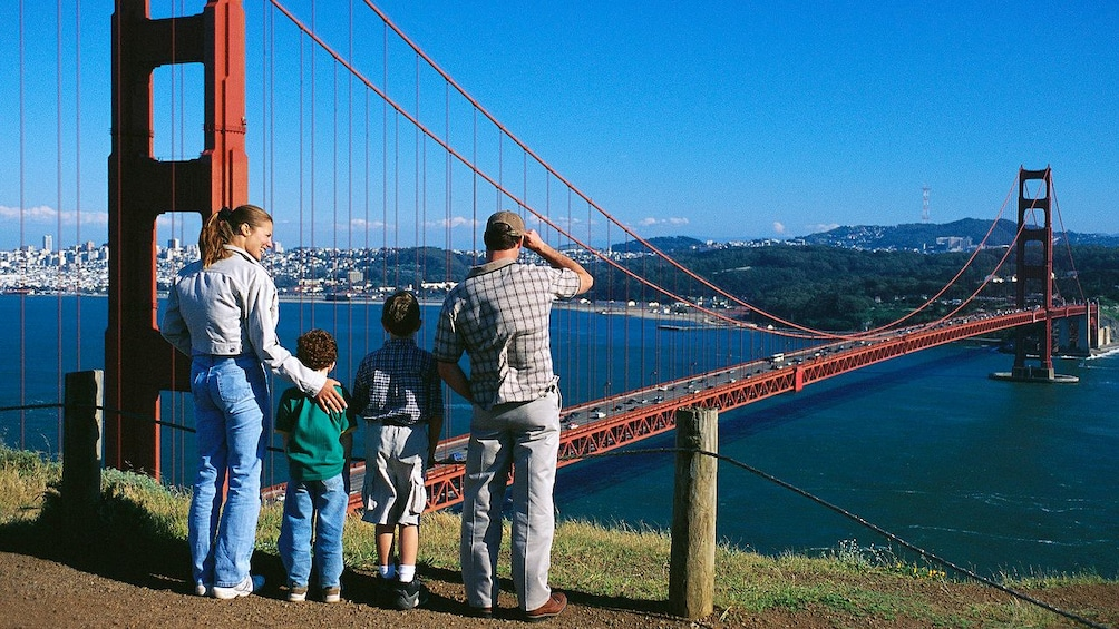 Show item 5 of 5. Family on a lookout point with a view of the Golden Gate Bridge in San Francisco
