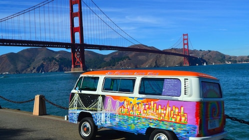 Colorfully painted tour van with the Golden Gate Bridge in the background in New York