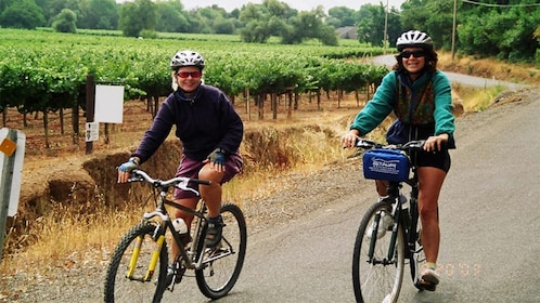 Pair of women riding bicycles near a vineyard in Carneros