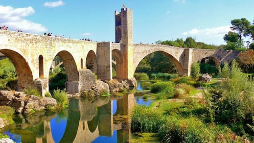 Watery reflection of the old stone bridge in Spain
