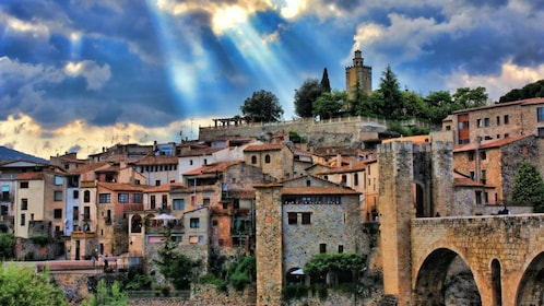 Beams of light shining down on a historic town in Spain