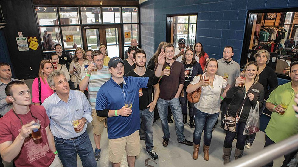 group holding up beverages at the brewery in Atlanta