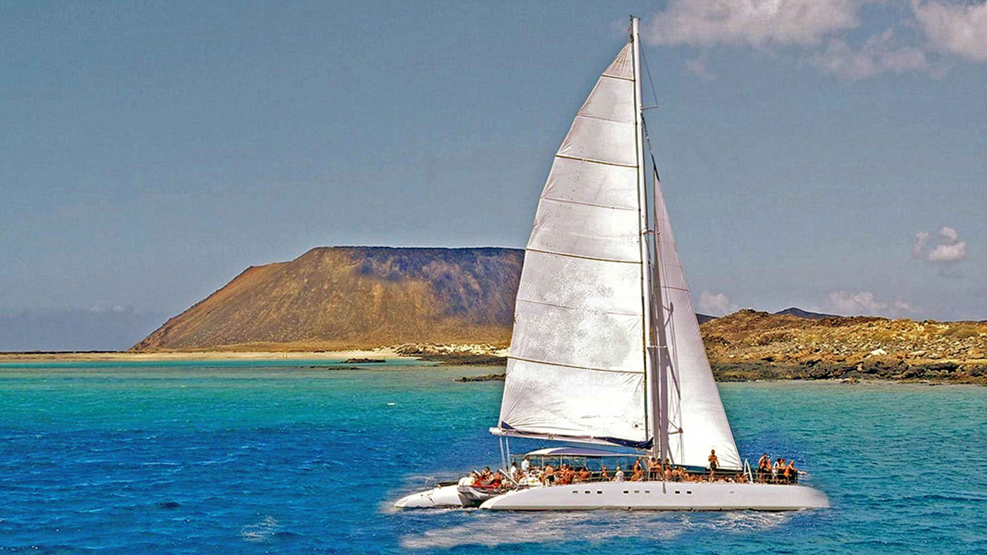 Boat sailing on the water with guests aboard in Catamaran Cruise to Playa de Papagayo