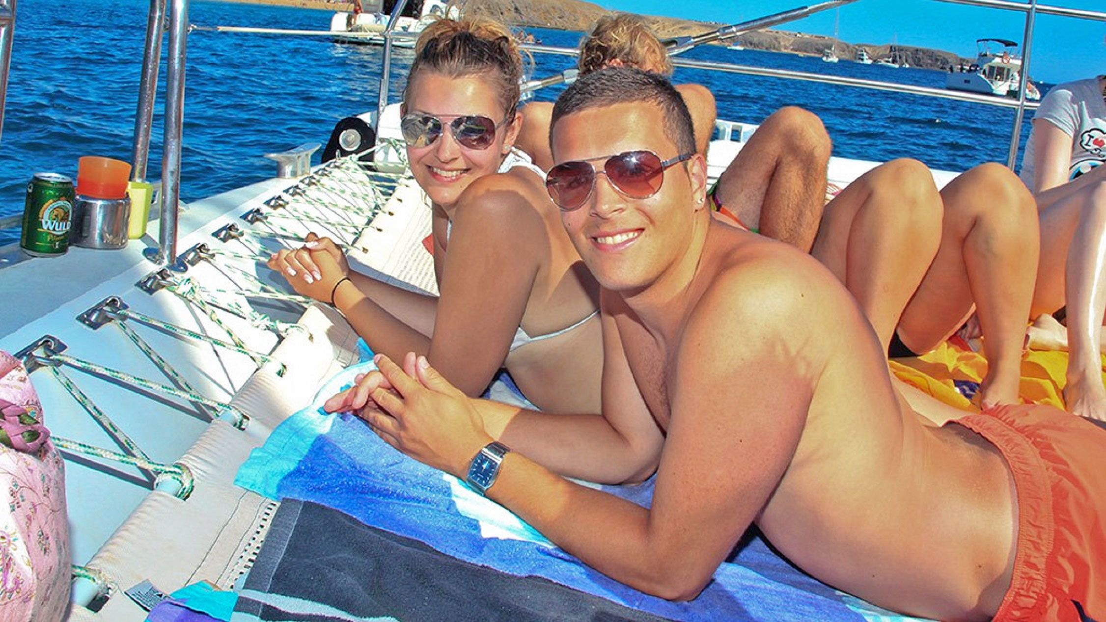 Couple sunbathing aboard a Catamaran Cruise to Playa de Papagayo