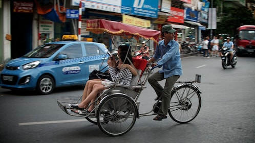 Mother and daughter in a rickshaw in the city in Hanoi