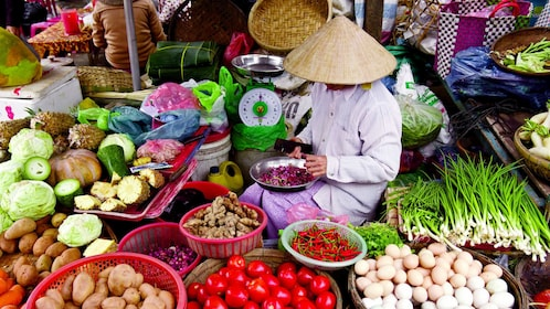 Vendor surrounded by fruits and vegetables at a market in Hanoi