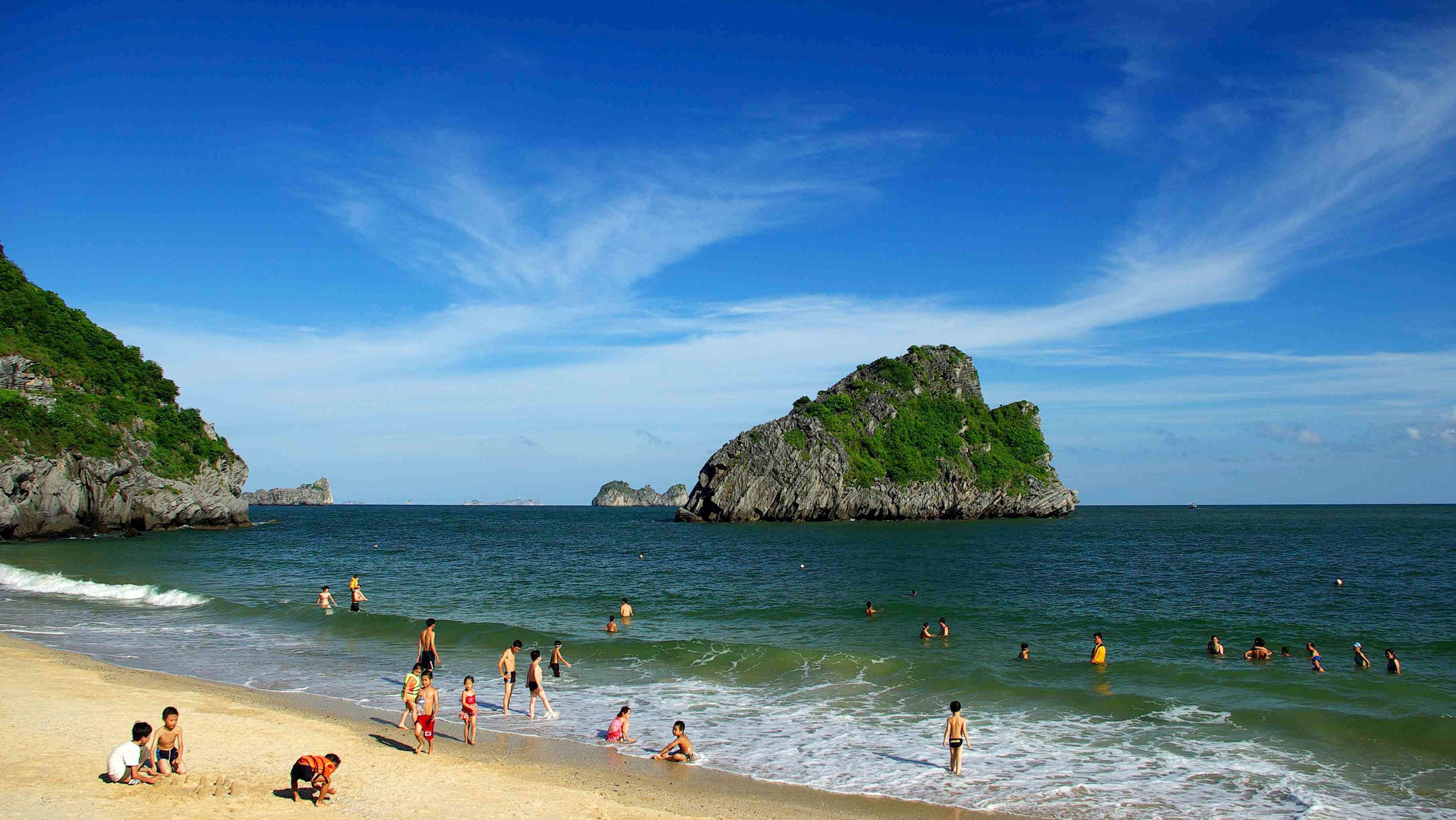 Beachgoers playing in the water in Halong Bay