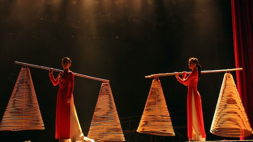 Women carrying large conical props during the Mist Dance Show in Ho Chi Minh City