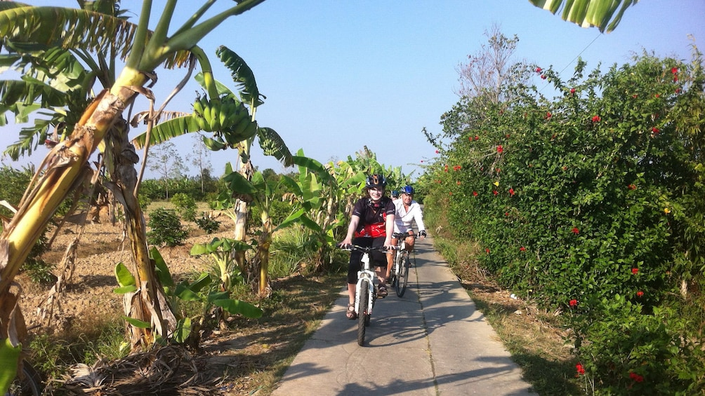 Show item 3 of 9. Bicycling group on a narrow path on a farm in Saigon