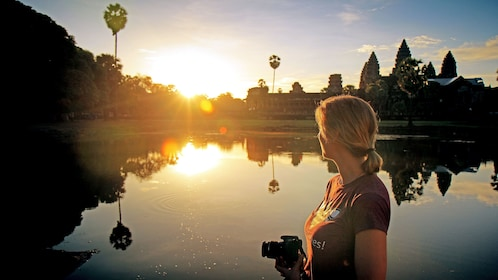 Woman with camera and Angkor Wat in the background at sunset in Siem Reap