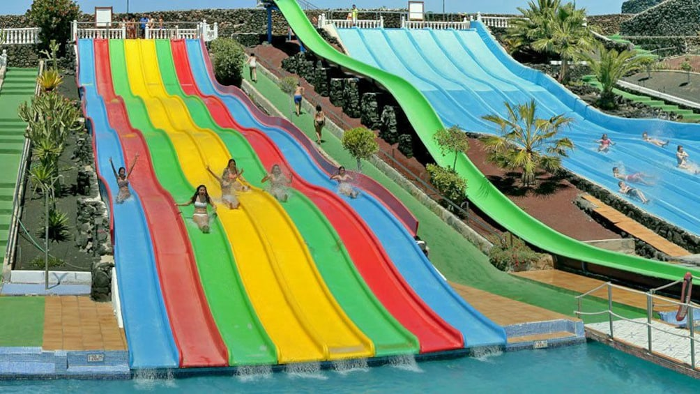 girls going down a waterslide next to one another in West Africa