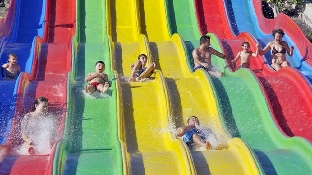 group sliding down a wavy water slide at the waterpark in West Africa