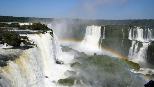 rainbow forming over the waterfalls in Brazil