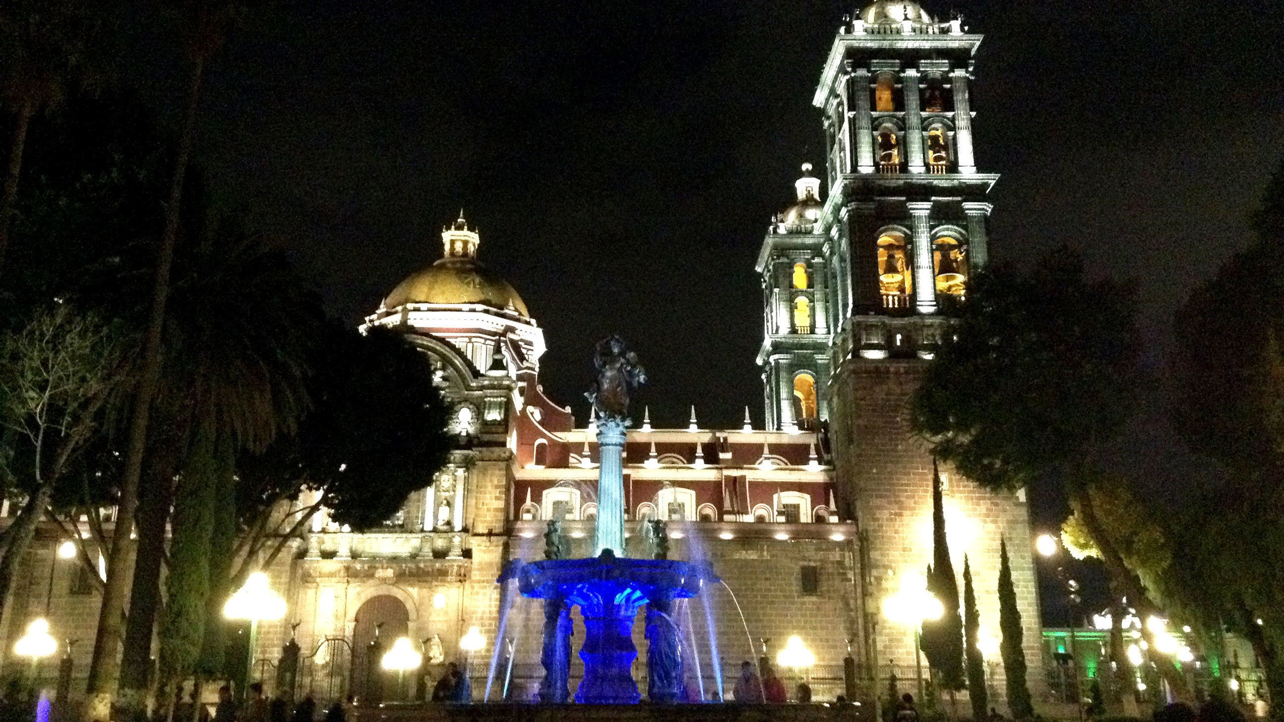 Glowing water fountain in front of cathedral in Puebla