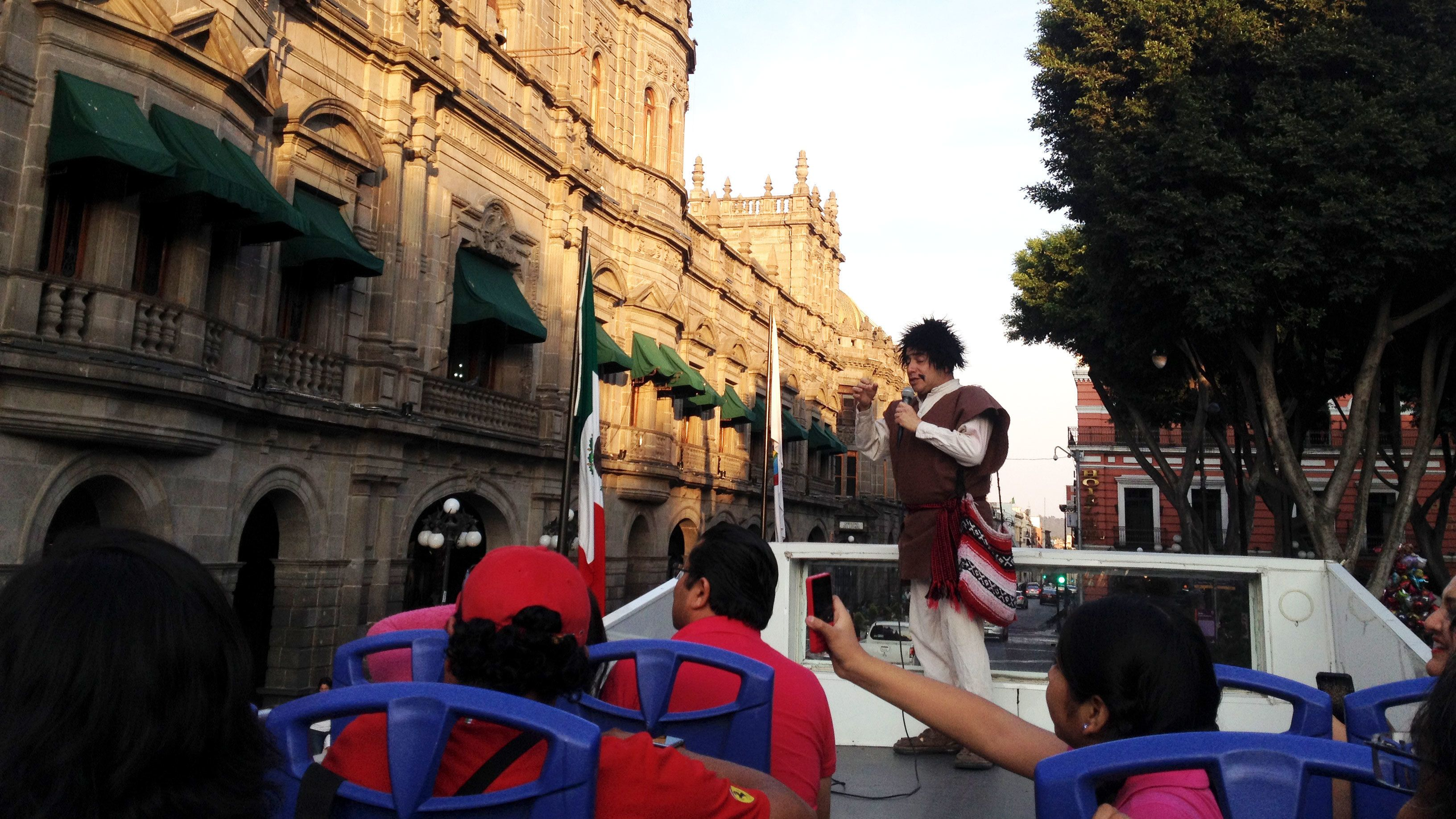 Tour guide talking to tourists on bus in Puebla