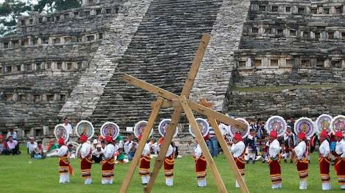 People in traditional attire performing a ceremony in front of the pyramid in Cuetzalan
