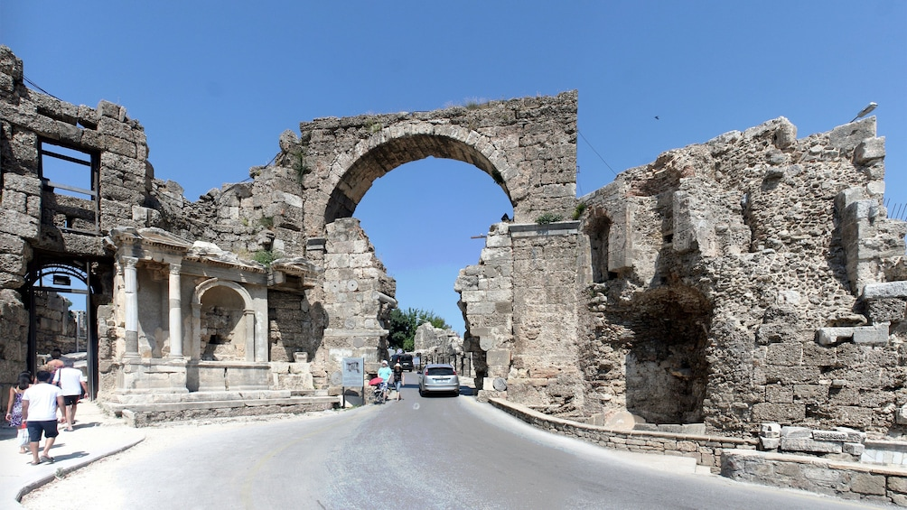 Show item 4 of 5. A car driving under an ancient stone archway at the ruins of Perge