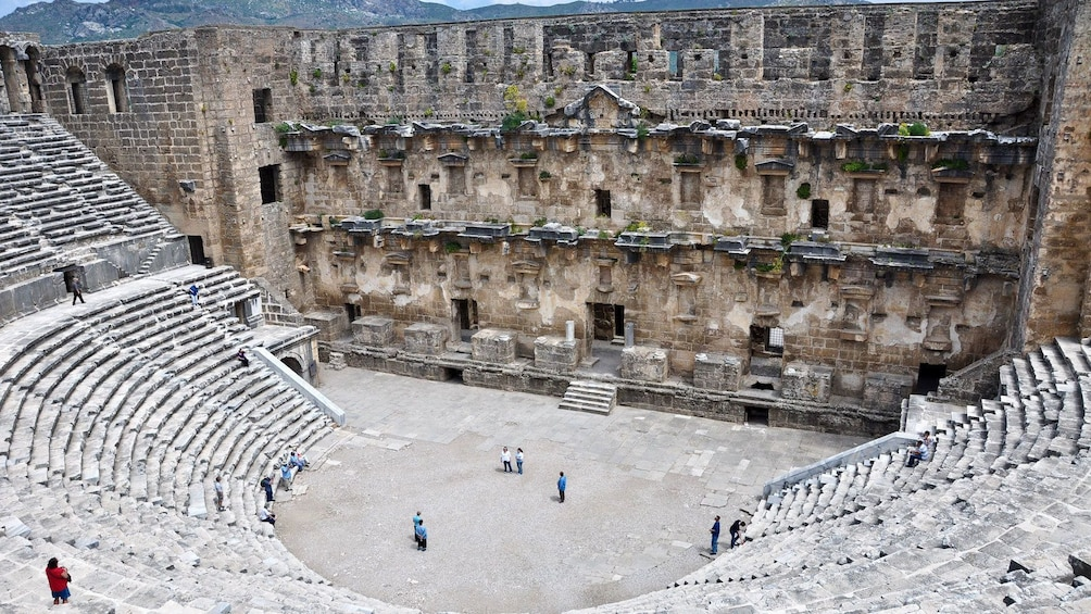Show item 2 of 5. People stand in an amphitheater in Perge
