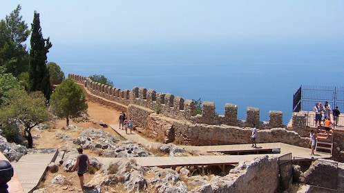 People walking along coastal castle walls in Antalya