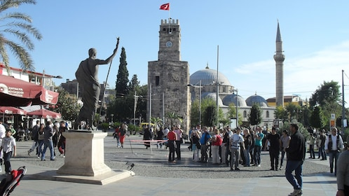 Groups of people gathered around historical monuments in Antalya