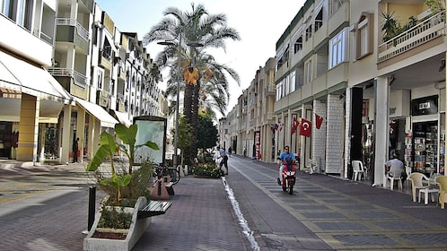 A person on a scooter riding past storefronts in Antalya