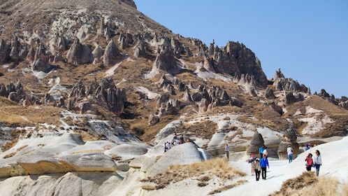 people walking along a rocky path in Cappadocia