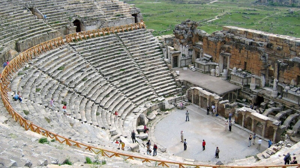 Show item 3 of 5. People standing in the remains of an amphitheater in Pamukkale